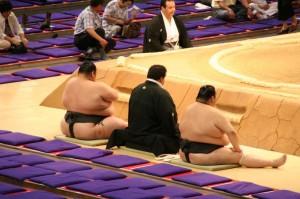 Un des arbitres au bord du dohyo, entouré de deux lutteurs de bonne envergure